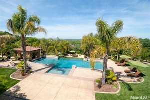 The five-acre lot features an expansive, sparkling blue pool in the backyard.