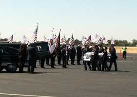 Family and friends watch and salute the fallen soldier.