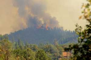 Smoke and fire are visible in Tuolumne City as the Rim Fire continues to burn nearby.