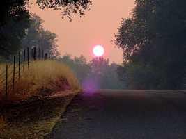 At sunrise, smoke-filled skies are visible.