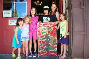 "A few of the photos show Corinna Logh, owner of The Iron Door Restaurant, gathering up her kids and some friends to personalize one ""thank-you"" sign."