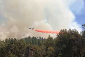 A plane streaks across the sky, dropping retardant on the Rim Fire. Do you have any photos we should see? Submit us your pictures and videos through KCRA u local.