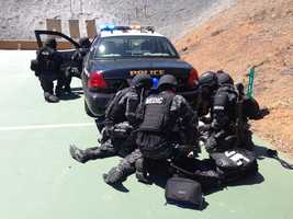 In this training scenario, the SWAT team rescues an officer shot in his car.