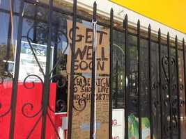 """A """"get well soon"""" sign is posted outside the store."""