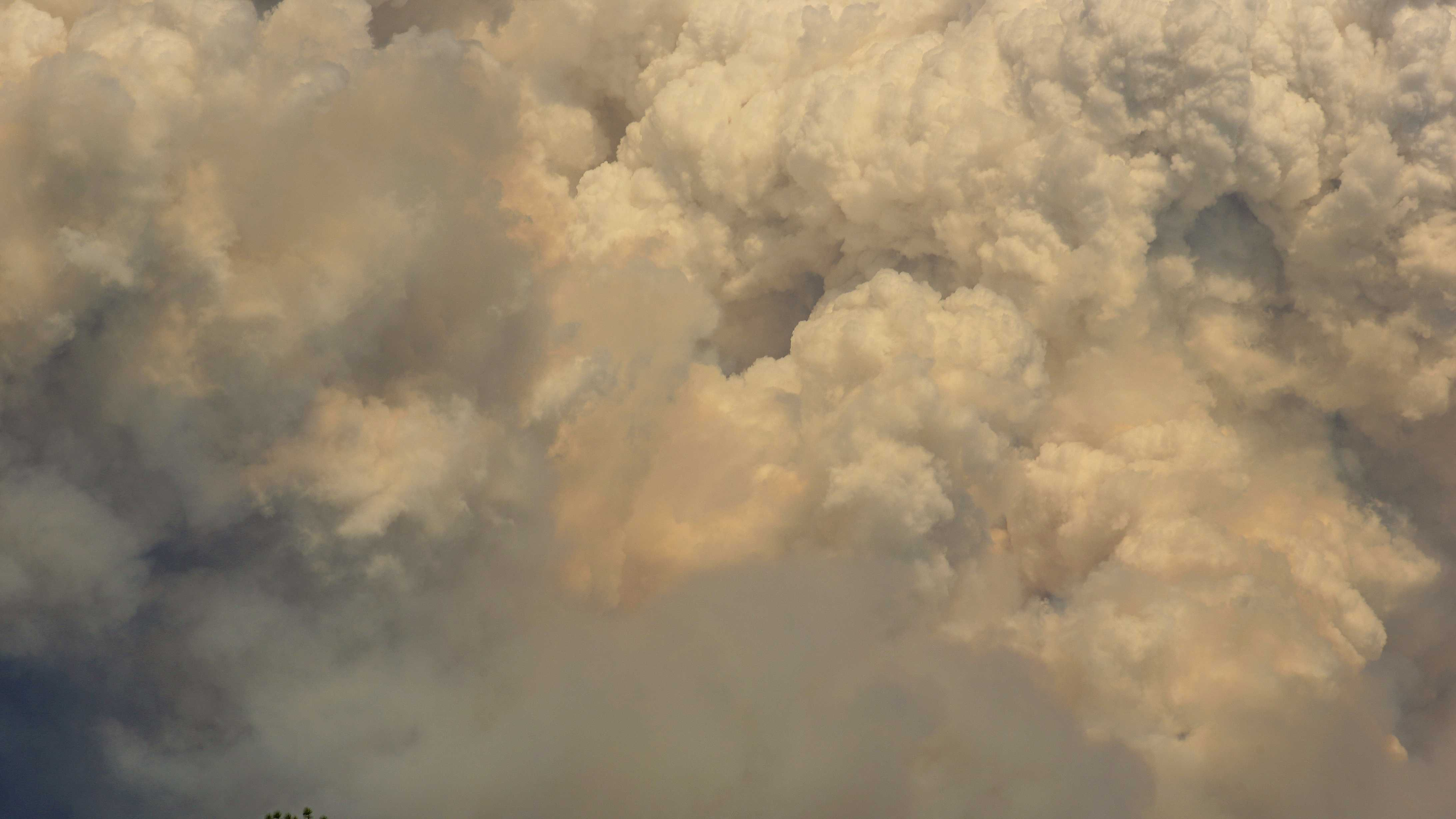 Plumes of pyrocumulus clouds originate from Rim Fire as seen from the town of Tuolumne.