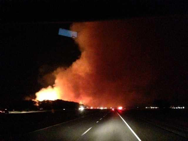 A fire at a hay field in Winters is sending plumes of smoke into the air near a major interstate.
