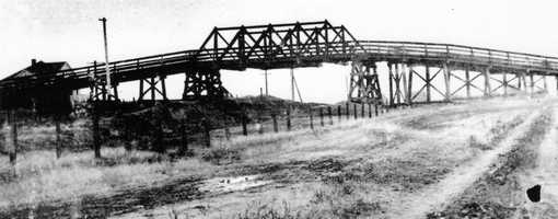 This 1907 photo shows the wooden bridge. In 1929, the bridge was rebuilt because locals feared that the wooden structure could catch fire due to its proximity to passing locomotives.