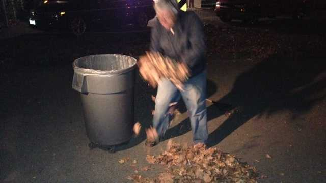 Ray Wagner picks up leaves he raked Friday morning.