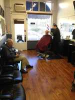 A patron sits and waits inside the 1920s-era barber shop, which is currently owned by Dave Keen. He is the third owner since 1923 and maintains the atmosphere of years past.