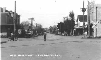 """The small farm town began to grow as the railroad industry boomed. Here's a view of Main Street-- now known as Elk Grove Boulevard -- looking west near the railroad track were a sign warns """"Look out for the cars."""""""