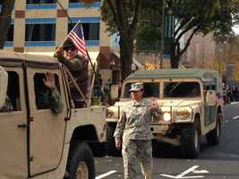 Military vehicles drive the parade route (Nov. 11, 2013).