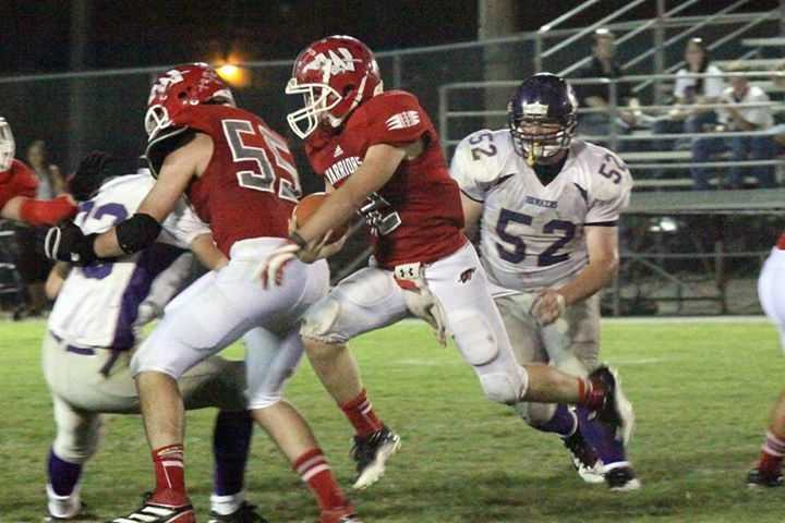 #37 - Winters Warriors players work together to get the football across the line of scrimmage.