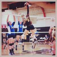 #38 - A Yuba City volleyball player spikes the ball over the net despite two blockers on the other side.