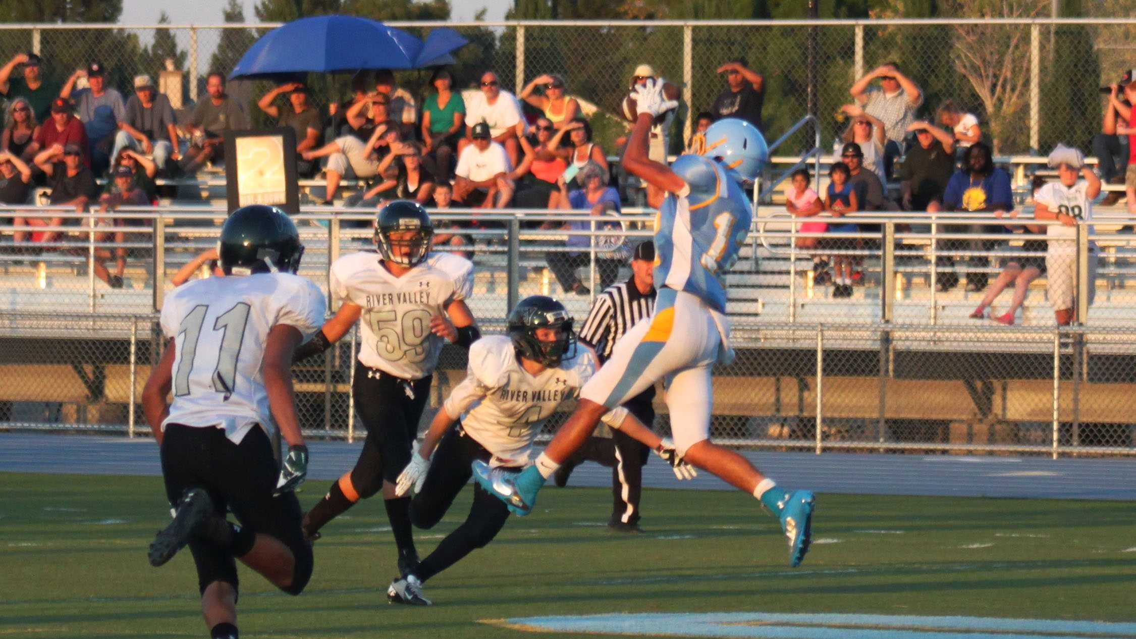 #46 - A player for the Center Cougars jumps up to grab the football as a few River Valley players run towards him.