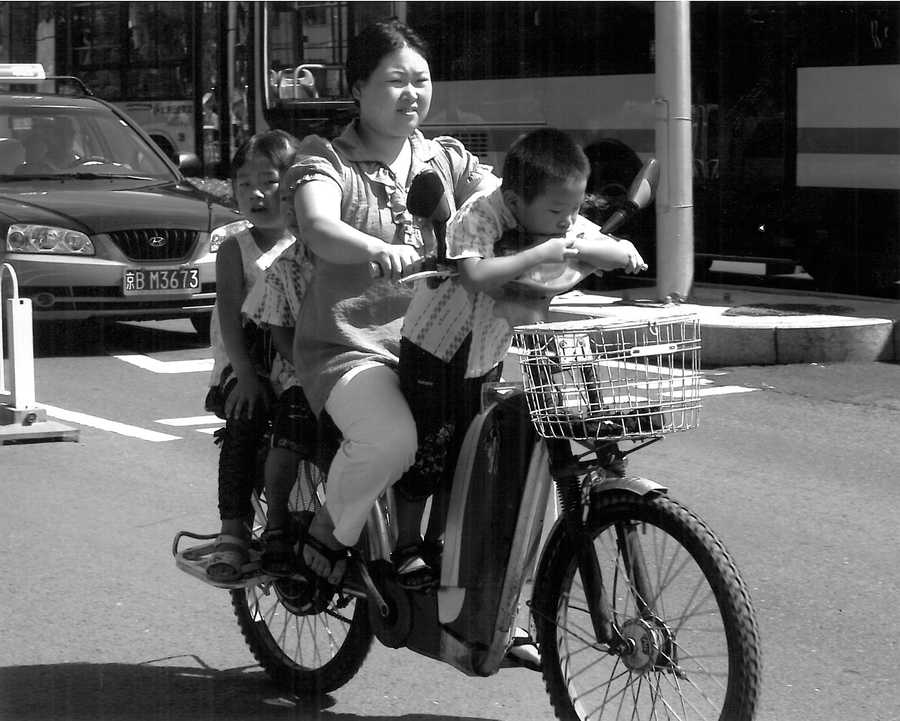 """15.) I love to take pictures. I shot this on the streets of Beijing and call it """"a bicycle built for three."""""""