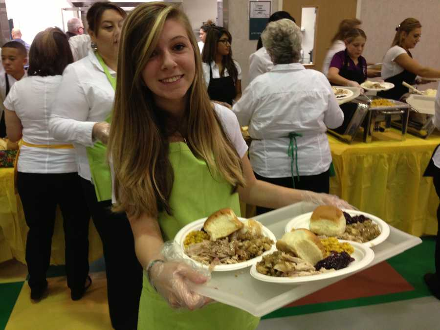 Emily Uyeno balances three plates as she serves Thanksgiving dinner at the Pannell Community Center in Sacramento.