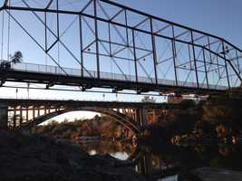 The steel truss bridge was moved for a number of years, but was placed back in its original location, next to the Rainbow Bridge. It is now only open to foot and bicycle traffic.