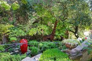 The back yard escape includes an outdoor kitchen bar, specially sculptured bronze trees, an outdoor limestone fireplace and a waterfall-fed pond crossed by a charming footbridge.