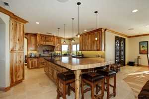 The gourmet kitchen features granite counters, a built-in refrigerator and freezer, double ovens, an island with a second sink and a raised eating area.