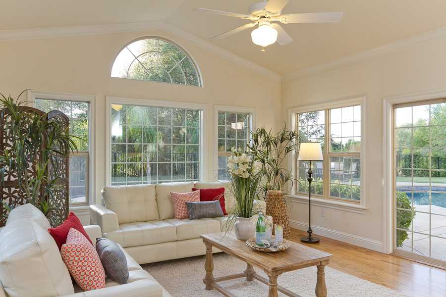 Sun bathe inside the sunroom while enjoying views of back property and sparking pool.