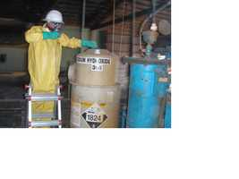 A worker with the California Department of Toxic Substances Control works with a tank of sodium hydroxide during cleanup of the former wood treatment facility outside of Elmira.