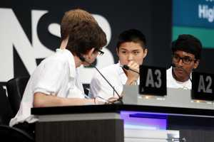 The Science Bowl teammates look to one another for guidance as they deliberate.