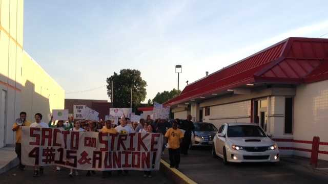 Demonstrators march outside the drive-thru window of the McDonald's on Howe Avenue.