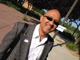 """A man gets a """"I vote"""" sticker early Tuesday morning in Sacramento."""
