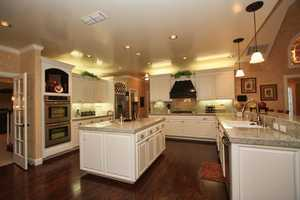 Anyone who loves to cook -- or enjoys a good meal -- will fall for the kitchen, which has sharp-white custom cabinetry complete with accented features.