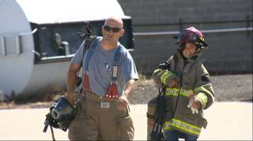 Isabelle Ford walks with her dad, firefighter Zachery Ford, at Kid's Camp. Ford is a volunteer instructor at the summer event.
