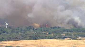 A four-alarm grass fire is kicking up a large amount of smoke near Cal Expo on Friday afternoon. (July 4, 2014)