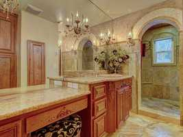 This bathroom is filled with details, from custom tile work and cabinetryto a handsome chandelier.