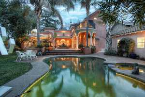 The backyard is secluded, features an open courtyard and pool and leads to the home's guest quarters.