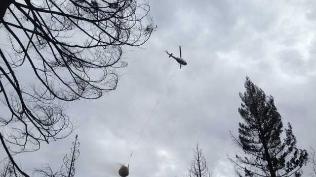 A helicopter carries a netful of rice straw to the King Fire burn zone.