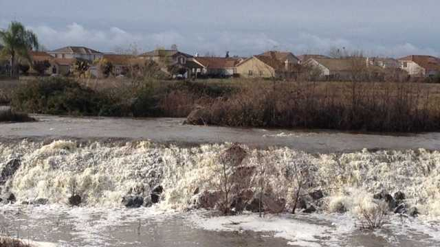 Water runoff from Laguna Creek in Elk Grove goes over artificial falls near Highway 99 on Friday.  (Dec. 12, 2014)