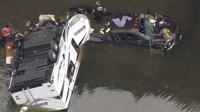 The truck driver was trapped in his vehicle for a short time, but firefighters freed him about 4:15 p.m. The truck and trailer remain in the water. (March 11, 2015)