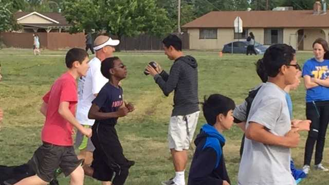 Students from Glen Edwards Middle School run alongside one of two dads attempting to run 125 miles in 24 hours.