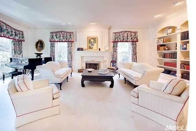 The formal living room with enhanced custom crown molding and lighted bookcases gives the home a presidential feel.