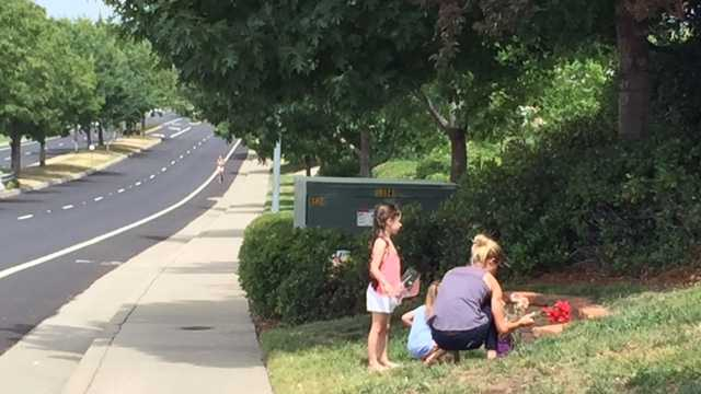 Neighbors lay flowers at the site of Monday's fatal bicycle crash in Folsom.