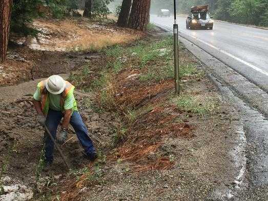 A Caltrans worker clears a clogged culvert after a downpour and flash flood swept into an area along Highway 50 in Kyburz.