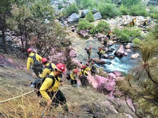 Pink fire retardant was laid down by planes and crews climbed through the steep terrain to get to the Kyburz Fire.