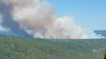 Smoke rose up over the forest in Nevada County as the Lowell Fire continued to spread.