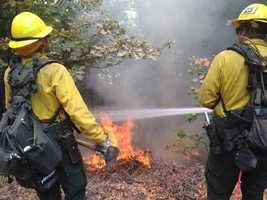 This photo from KCRA reporter Mike Luery shows two firefighters battling a hot spot from the Lowell Fire.