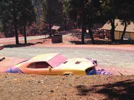 The so-called Lowell Fire broke out July 25 in Nevada County. In this photo, pink fire retardant covers a car and the ground.