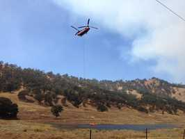 A Cal Fire helicopter gets water for an air drop on the Rocky Fire.