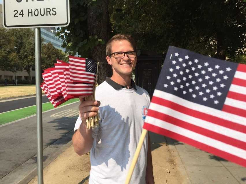 John handed out free flags Friday morning at Eight Street and Capitol Mall. (Sept. 11, 2015)