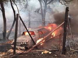 Flames from the so-called Butte Fire burn a car along Mountain Ranch Road. (Sept. 11, 2015)