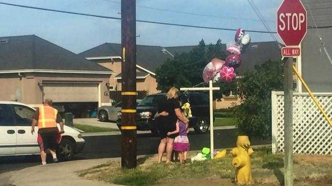 Families near Shasta Elementary School leave flowers and balloons at the crash site where a 6-year-old Manteca girl was killed Friday. (Sept. 25, 2015)