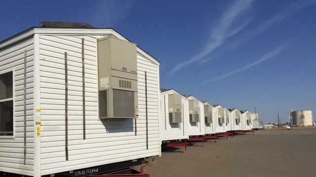 About 60 mobile homes provided by FEMA sit on a parking lot in North Highlands.