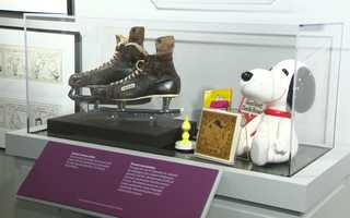 """Speaking of ice skating, Charles M. Schultz was a lover of the ice and especially ice hockey. His family donated his well-used ice skates, which sit next to some classic """"Peanuts"""" items."""